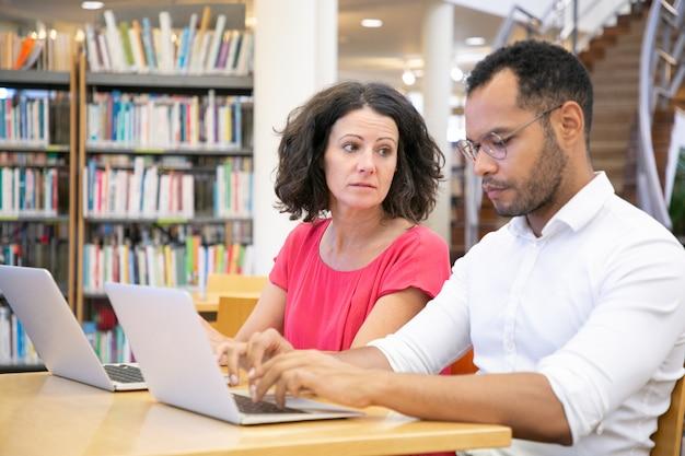 Dos estudiantes universitarios adultos que trabajan en la clase de informática de la biblioteca