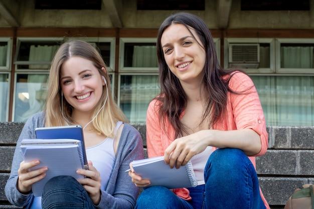 Dos estudiantes universitarios que estudian juntos al aire libre