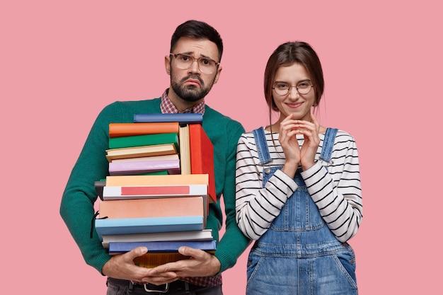 Dos estudiantes universitarios sostienen libros de texto, se preparan para el examen final, usan gafas