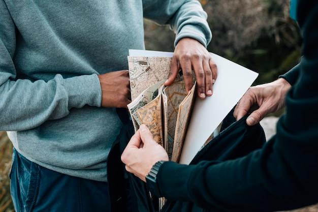 Dos excursionistas masculinos buscando mapa en la mochila
