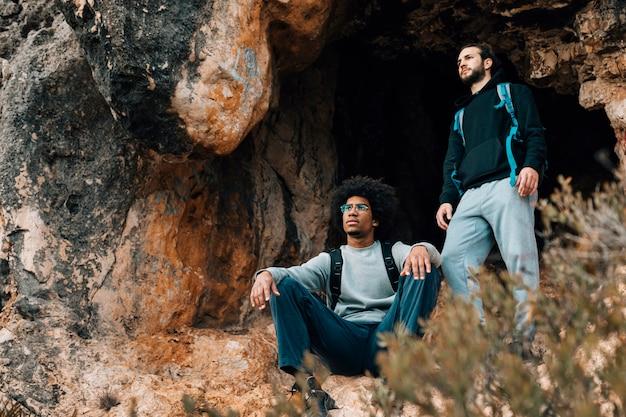 Dos excursionistas masculinos cerca de la entrada de la cueva