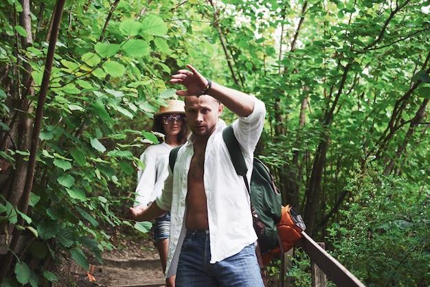 Dos excursionistas con mochilas en la espalda en la naturaleza.