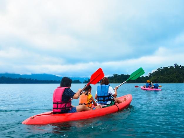 Dos familias paseos en bote, kayak en el río presa