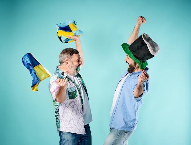 Los dos fanáticos del fútbol con una bandera de ucrania sobre azul