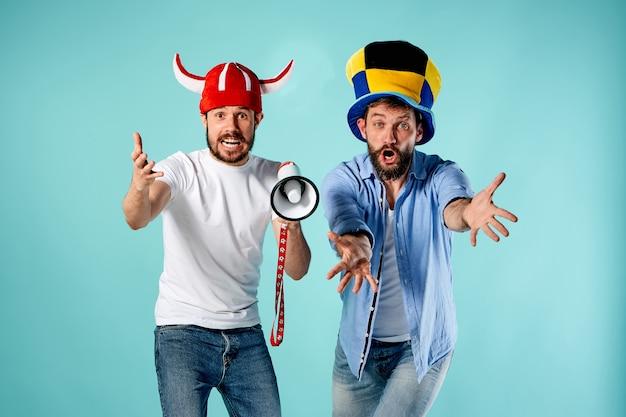 Los dos fanáticos del fútbol con boquilla sobre azul