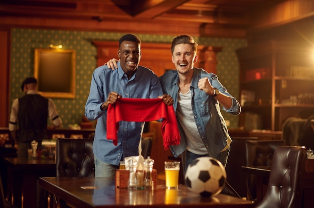 Dos fanáticos del fútbol masculino con bufanda roja y pelota viendo la transmisión de televisión del juego, amigos en el bar