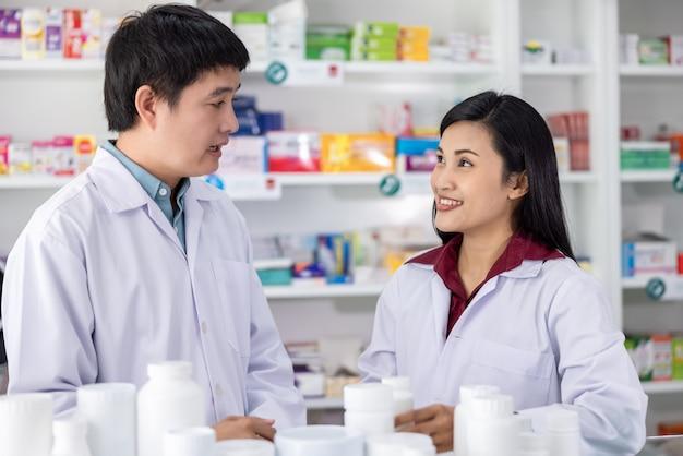 Dos farmacéuticos masculinos y femeninos sonriendo felices de servicio en farmacia tailandia concepto de salud y negocio