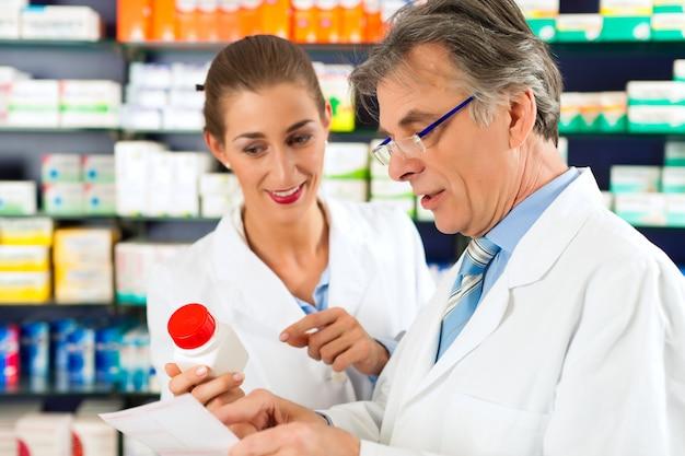 Dos farmacéuticos con productos farmacéuticos en la mano consultándose en una farmacia.