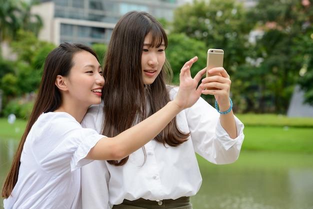Dos felices jóvenes hermosas mujeres adolescentes asiáticas tomando selfie juntos en el parque