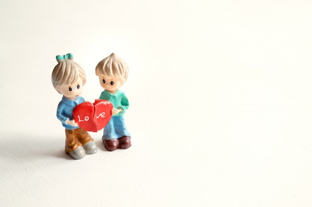 Dos figuras niño y niña con las mitades de corazón rojo.
