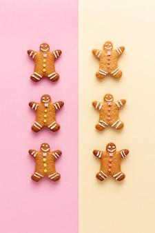 Dos filas de hombres de pan de jengibre de navidad sobre fondos de color rosa y amarillo