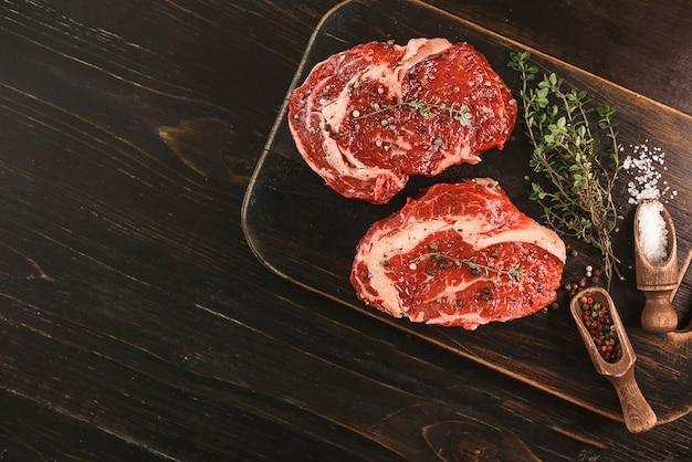 Dos filetes de carne marmoleada cruda en aceite de oliva y especias listas para freír.