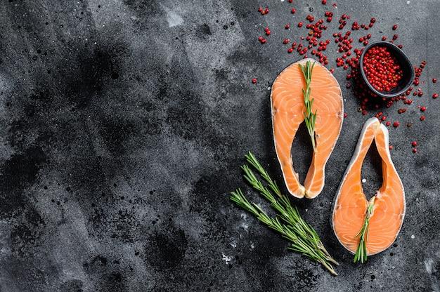 Dos filetes de salmón crudo fresco con pimienta y romero. espacio negro. vista superior. copia espacio