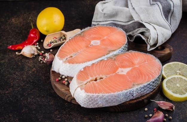 Dos filetes de salmón crudo fresco en tablero de pizarra con sal, pimientos, limón en la mesa oscura, vista superior. concepto de comida de dieta saludable