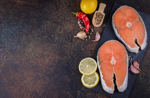 Dos filetes de salmón crudo fresco en tablero de pizarra con sal, pimientos, limón sobre fondo oscuro de la mesa, vista superior. concepto de comida de dieta saludable