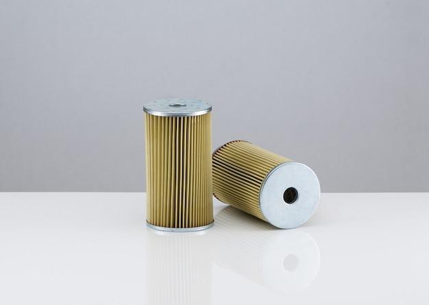 Dos filtros de automoción de forma cilíndrica sobre un fondo blanco con reflexión