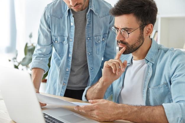 Dos financieros exitosos y elegantes, analizan documentos comerciales, trabajan en un nuevo proyecto de inicio