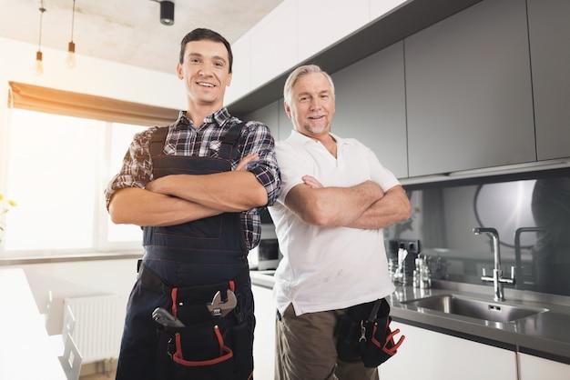 Dos fontaneros masculinos que presentan en la cocina. armas acimbo.