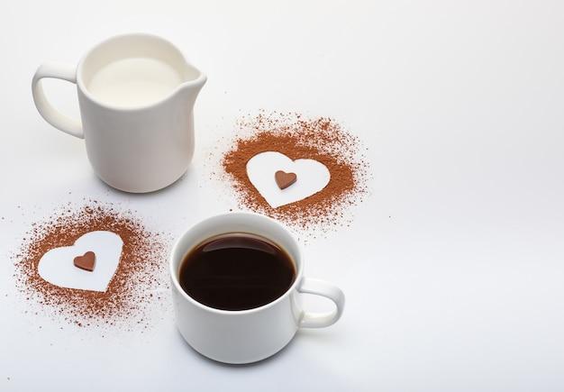 Dos formas de corazón de cacao en polvo, una taza de café con leche y copia espacio sobre fondo blanco.
