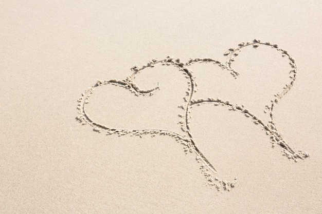 Dos formas de corazón dibujado en la arena