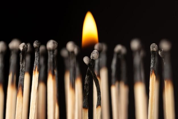 Dos fósforos con un pequeño fuego encima de ellos, uno cerca del otro.