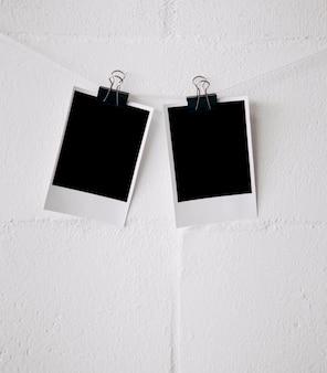 Dos fotos polaroid en blanco atadas en una cuerda con clips de bulldog contra la pared