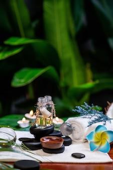 Dos frascos de aceites aromáticos colocados sobre piedras para una piedra de terapia y ubicados en una toalla junto a la cual yace una flor, hay esferas transparentes, una toalla enrollada y una ramita de lavanda