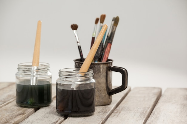 Dos frascos de pinceles de acuarela y pintura sobre mesa de madera