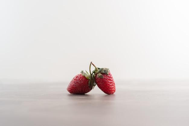 Dos fresas frescas en la mesa de mármol.