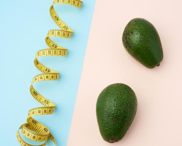 Dos frutas de aguacate verde y una cinta amarilla de medición retorcida sobre un fondo beige-azul