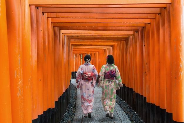 Dos geishas entre tori gate de madera roja en la capilla de fushimi inari en kyoto, japón.