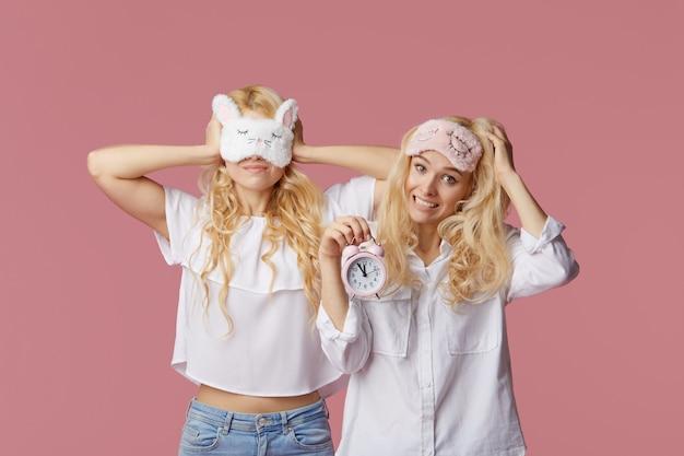 Dos gemelas jóvenes insomnes en pijama y antifaces para dormir en una pared rosa. despertador despertó a la mujer
