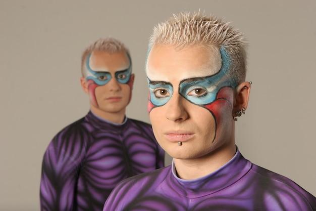 Dos gemelos con cabello blanco en ajustados trajes morados posando para la cámara, superhéroes