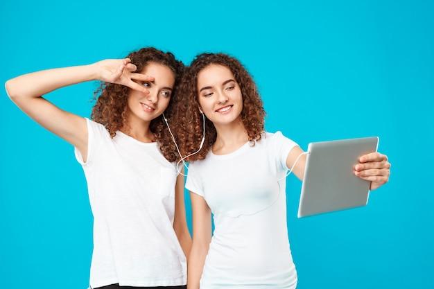 Dos gemelos de mujer haciendo selfie en tableta sobre azul.