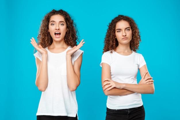 Dos gemelos de mujer joven posando sobre azul.