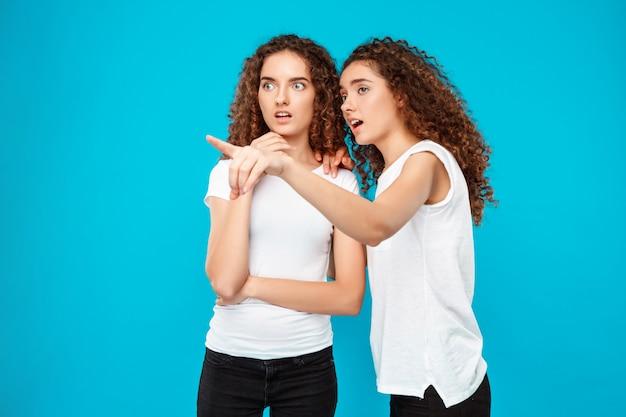 Dos gemelos sorprendidos de la mujer que señalan con el dedo lejos sobre azul.