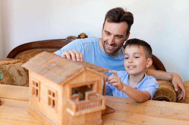 Dos generaciones de hombres, padre e hijo, juegan con un constructor de madera que parece una casa real con balcón, ocupado con el proceso de instalación de un techo de juguete.