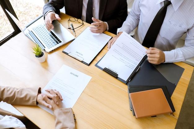 Dos gerentes del comité de selección leen un currículum durante una entrevista de trabajo para hablar sobre el reclutamiento