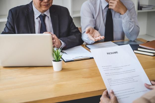 Dos gerentes hacen preguntas al solicitante sobre el historial de trabajo, el sueño coloquial, la habilidad y la experiencia