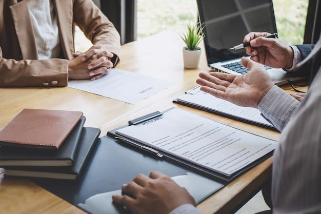 Dos gerentes leen un currículum durante una entrevista de trabajo, entrevista con un empleador para preguntar a una mujer que busca trabajo