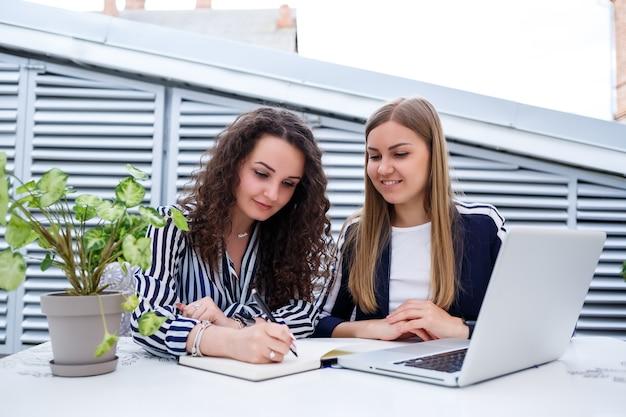 Dos gerentes de mujeres de negocios jóvenes exitosas están sentadas en una mesa con una computadora portátil y un cuaderno trabajando en un nuevo proyecto de desarrollo, las estudiantes escriben un informe sobre el trabajo de su computadora