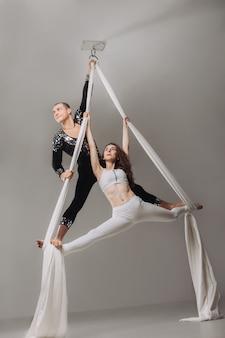 Dos gimnastas aéreas realizando acrobacias de seda.