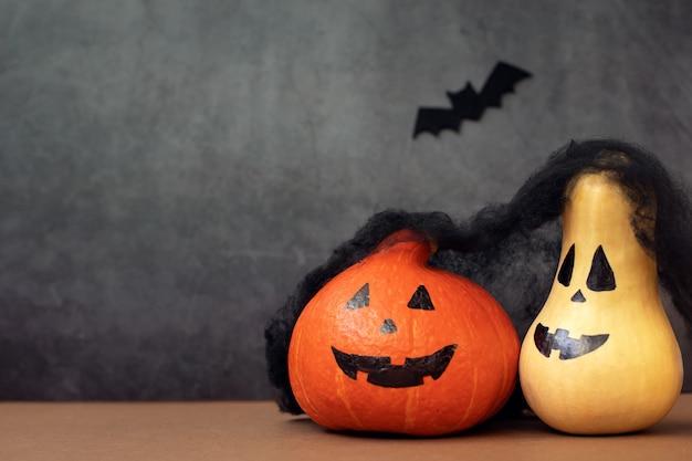 Dos graciosas calabazas de halloween con caras pintadas y murciélagos sobre un fondo gris oscuro ellos parte