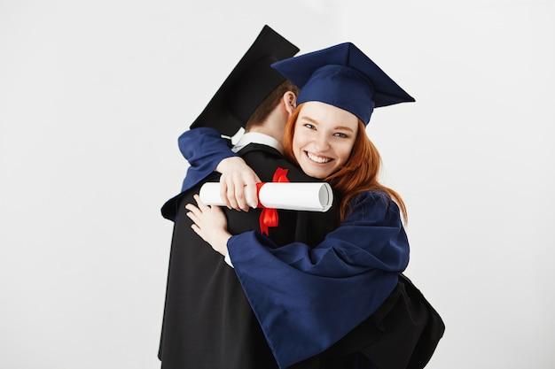 Dos graduados abrazando sobre superficie blanca ginger mujer sonriendo