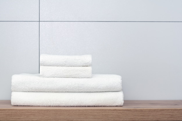 Dos grandes y dos pequeñas toallas blancas cuidadosamente dobladas se encuentran en un estante de madera contra el fondo de baldosas de cerámica.