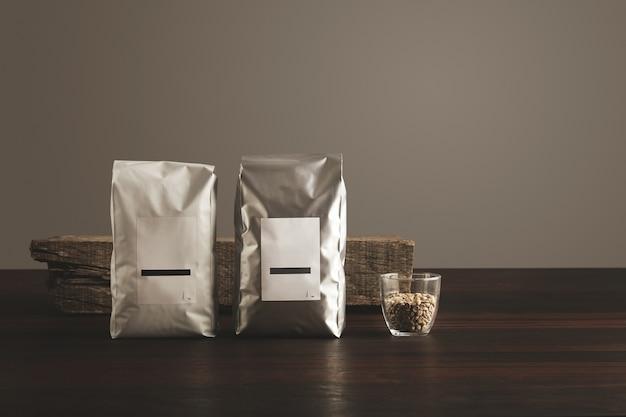 Dos grandes paquetes herméticos con etiquetas en blanco cerca de vidrio transparente con granos de café de muestra cruda