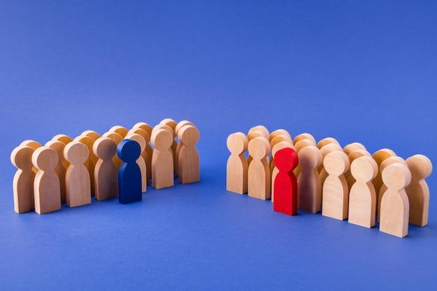 Dos grupos de figuras de madera miembros participantes de pie detrás de sus líderes