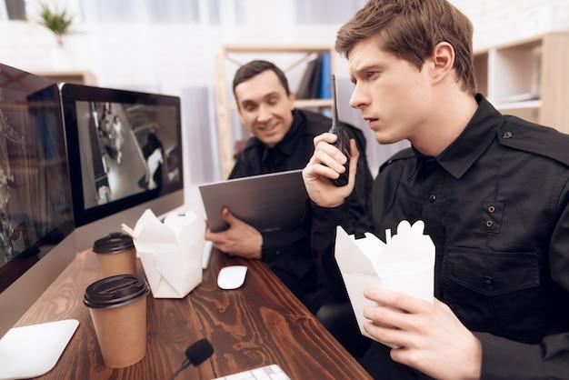 Dos guardias almuerzan en el lugar de trabajo en la sala de seguridad.