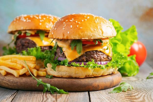Dos hamburguesas caseras frescas con patatas fritas.