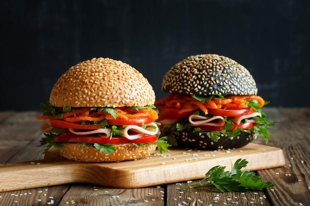 Dos hamburguesas con semillas de sésamo con verduras frescas tomate, pimiento, zanahorias picantes, perejil y jamón, claro y oscuro, sobre una tabla para cortar madera. fondo negro.
